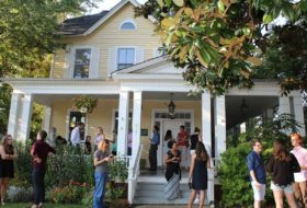 Two story yellow house with a large front porch with clusters of students and faculty chatting together