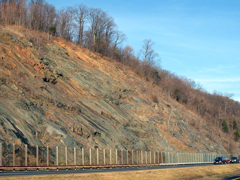 Large road cut along Interstate 64, with what appears to be a fence a little taller than the cars protecting the highway.
