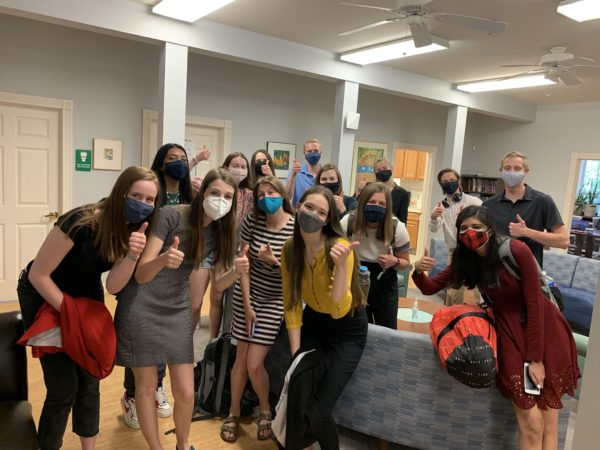 A group of masked students give thumbs ups in an open room around couches.