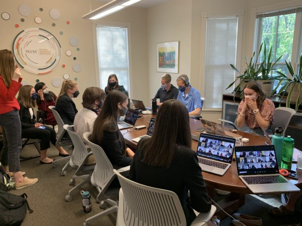 A group of 11 masked people around a conference table with laptops open with Zoom meetings in progress.