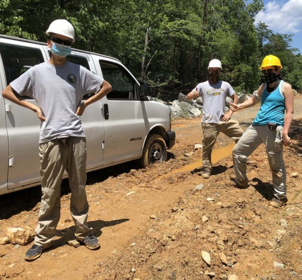 Three masked geologists standing beside a van in the mud