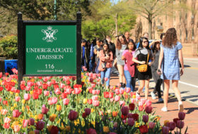 A campus tour group passes by the Undergraduate Admission sign surrounded by spring tulips