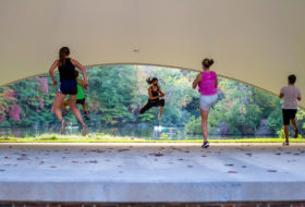 Several students in the air mid-jump during an outdoor BodyCombat FitWell Class at the Martha Wren Briggs Amphitheatre at Lake Matoaka