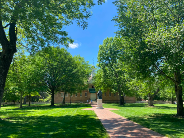 A wide brick walkway cuts through a green grassy area with lush trees, past a statue and ending at a historic brick building with a cupula.