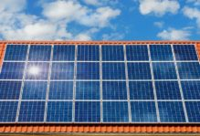 Solar panel on an orange roof with sunny skies above.