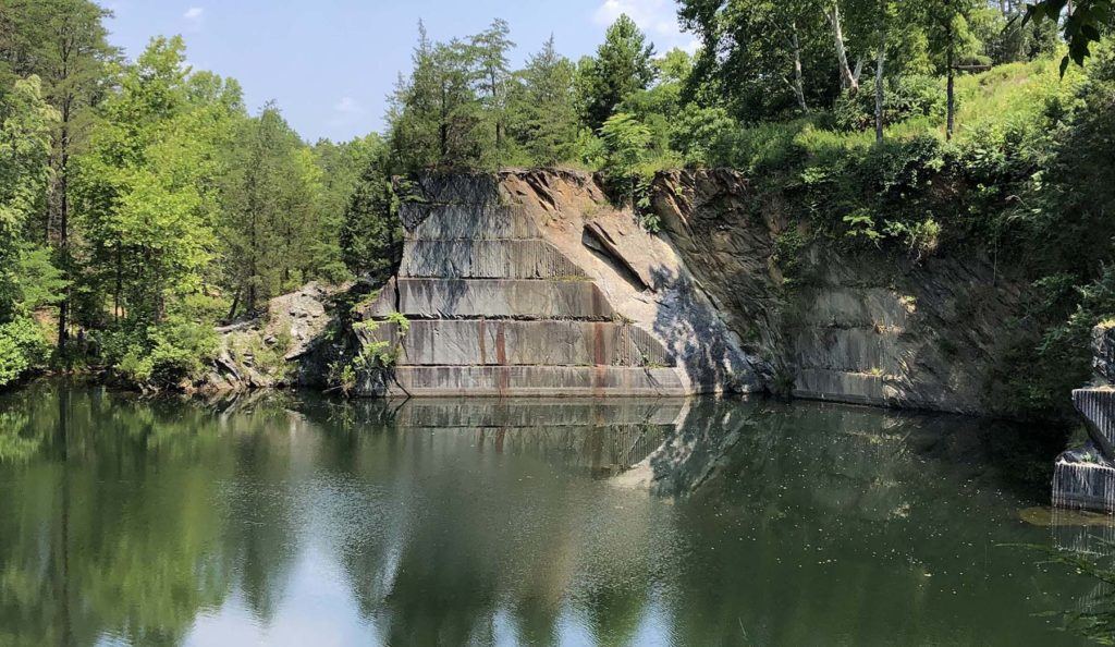 Wooded area around a body of water with steep cut rock walls.