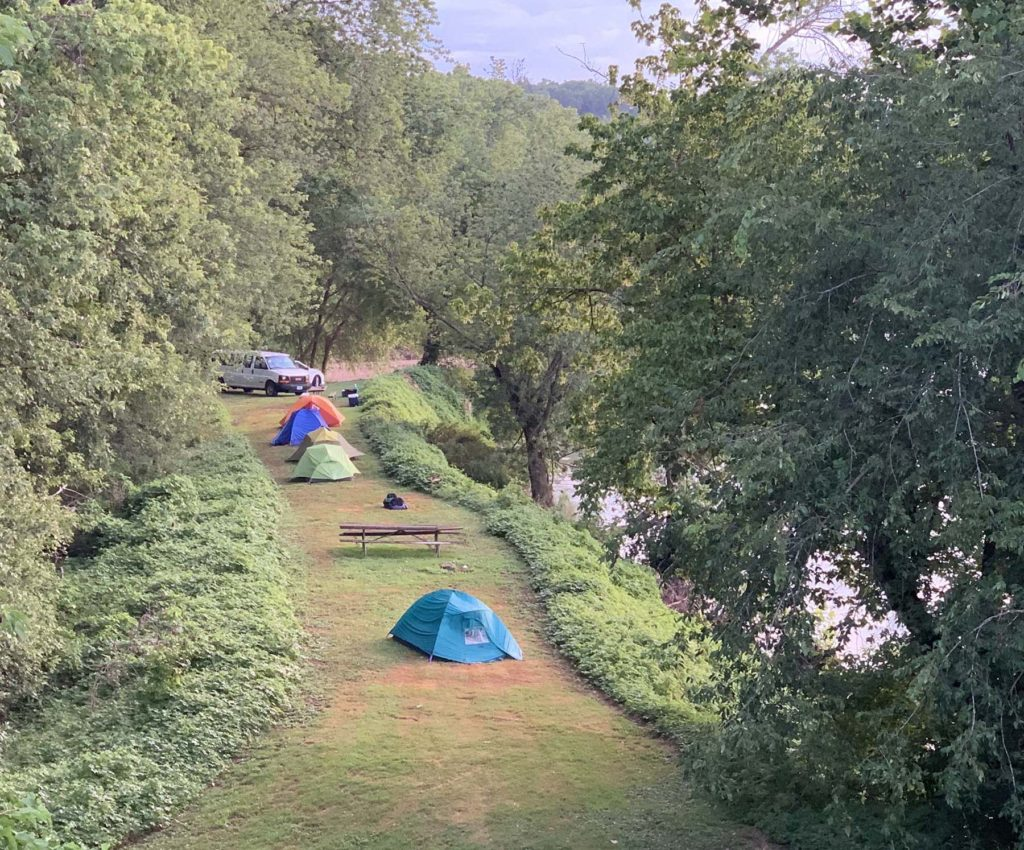 A narrow mowed area along a wooded river bank the team's tents, picnic table and van.