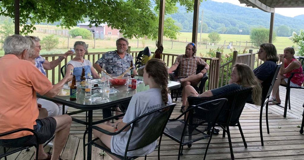 A group of nine people seated around a table with beverages and food, with a scenic view of farmland and mountains.