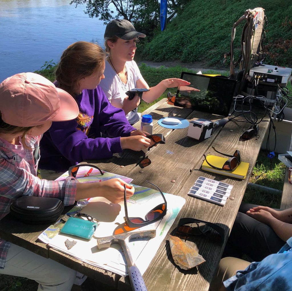 Several people at a wooden table covered with tools and instruments, situated on a river bank.