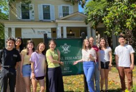 Nine smiling students pose with the Global Research Institute sign in the front yard of a yellow house.