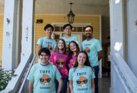 Seven smiling people wearing TUFF Cookie tshirts grouped on the porch of a large yellow house